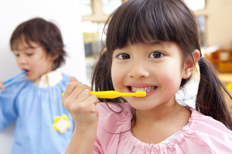 asian girl brushing her teeth